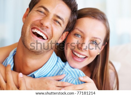 Closeup portrait of couple giving you an attractive smile with woman embracing man from behind