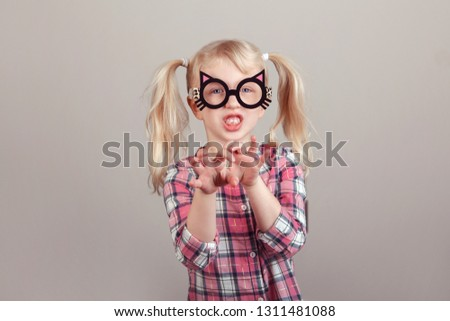 Closeup portrait of cute adorable blonde Caucasian preschool girl wearing funny cat glasses and playing, acting, making faces. Kid expressing emotions. April fool's day concept. #1311481088