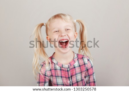 Closeup portrait of cute adorable white blonde Caucasian preschool girl smiling in front of camera in studio. Child laughing posing on plain light background. Kid expressing emotions #1303250578