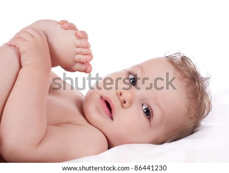 Closeup portrait of cute baby boy holding his feet