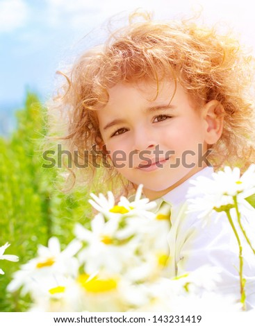 Closeup portrait of cute baby boy with beautiful curly hair on daisy field in sunny day, summer time concept