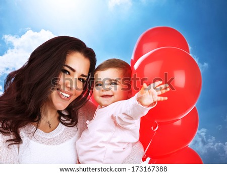 Closeup portrait of cute cheerful mother carry sweet baby daughter, having fun outdoors, playing with red balloons, happy family portrait