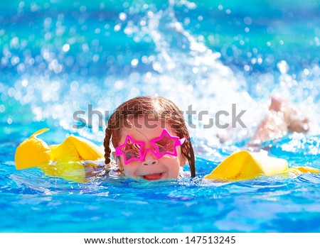Closeup portrait of cute little arabic girl swimming in the pool, happy child having fun in water, beach resort, summer vacation and holidays concept