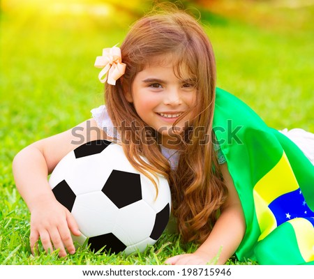 Closeup portrait of cute little football fan lying down on fresh green grass with ball and big Brazil flag, happy supporter of Brazilian football team