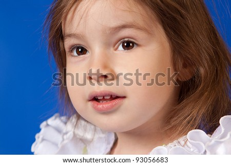 closeup portrait of cute little girls dressed in white on a blue background