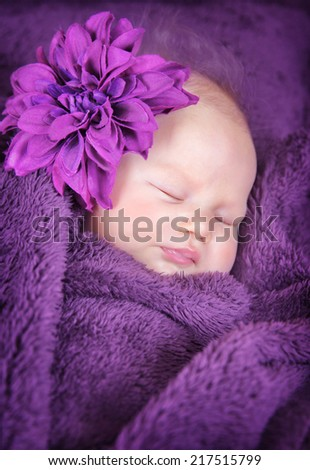 Closeup portrait of cute little newborn baby sleeping at home covered in purple blanket and wearing big stylish flower accessories, innocence concept