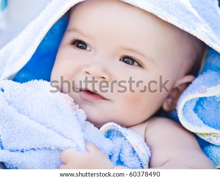 Closeup portrait of cute smiling baby boy in blue towel