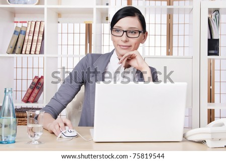 Closeup portrait of cute young business woman at her workplace in an office environment