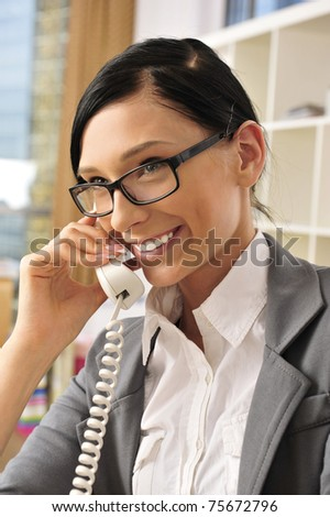 Closeup portrait of cute young business woman smiling at her workplace in an office environment. Talking by the phone