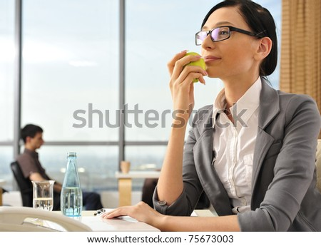 Closeup portrait of cute young business woman smiling at her workplace in an office environment. Eating green apple - stock photo