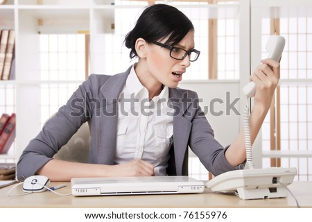 Closeup portrait of cute young business woman smiling at her workplace in an office environment