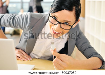 Closeup portrait of cute young business woman smiling. Sitting at her workplace using laptop and inserting usb