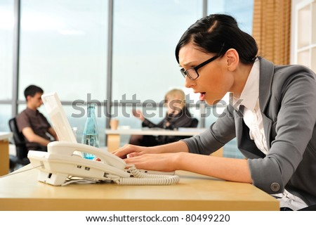 Closeup portrait of cute young business woman using laptop and looking at the screen at her workplace in an office environment. Her colleagues at the back. She is confused