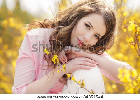 Closeup portrait of cute young girl with yellow flowers smiling outdoors #184351544