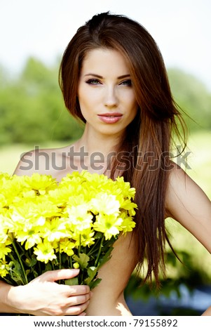 Closeup portrait of cute young girl with yellow flowers smiling outdoors