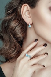 Closeup portrait of ear with hand and beautiful jewelry on it. Jewelry set of earrings and ring with gemstone.