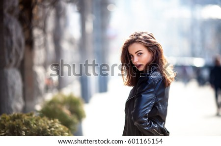 Closeup portrait of effective girl with long curly hair smiling to camera on street on building background. She wears leather jacket,urban backpack , bright red lips
