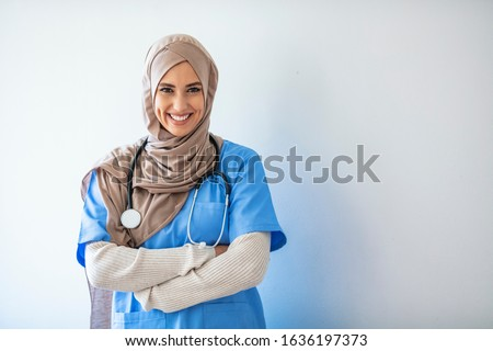 Closeup portrait of friendly, smiling confident muslim female nurse. Authentic Confident Middle Eastern Healthcare Worker. Middle age senior arab nurse woman wearing hijab over isolated background