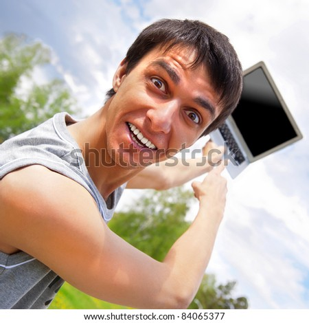 Closeup portrait of funky casual young man pointing at laptop screen outside at summer park