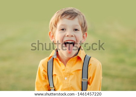 Closeup portrait of funny blond Caucasian preschool boy making faces in front of camera. Child showing tongue against plain light green background. Kid expressing emotions.  #1461457220