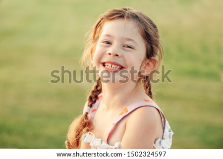 Closeup portrait of funny cute adorable smiling laughing Caucasian preschool girl with pigtails looking in camera against plain light green background outdoor at sunset. Kid expressing emotions.
