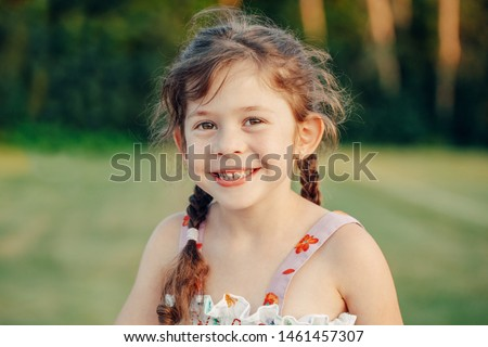 Closeup portrait of funny cute adorable smiling white Caucasian preschool girl with pigtails looking in camera against plain light green background outdoor at sunset. Kid expressing emotions.
