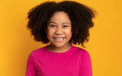 Closeup Portrait Of Funny Cute African American Little Girl Laughing At Camera, Posing Over Yellow Background In Studio, Free Space