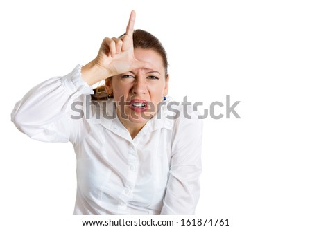 Closeup portrait of funny young woman displaying a loser sign with hand on her forehead, isolated on a white background with copy space. Negative human emotions facial expressions signs and symbols Stockfoto ©