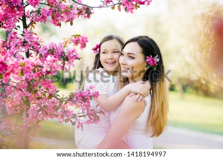 Closeup portrait of gentle gentle motherhood parenting feel satisfied am glad to have free time warm and cozy to cuddle the touch of a hand to wear stylish white clothes in spring flowers #1418194997