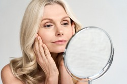 Closeup portrait of gorgeous happy middle age woman looking at mirror touching her skin enjoying treatment for dry skin. Advertising of antiaging beauty skin care products.