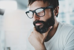 Closeup portrait of handsome bearded designer wearing eye glasses and working at the modern lightful office loft.Horizontal. Blurred background