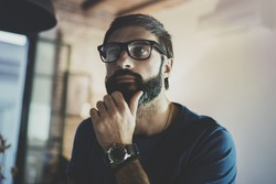 Closeup portrait of Handsome bearded man spending rest time at the modern home at evening.Horizontal. Blurred background
