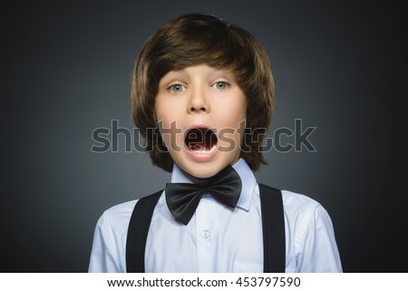 Closeup Portrait of handsome boy with astonished expression while standing against grey background #453797590