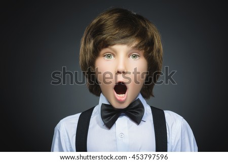 Closeup Portrait of handsome boy with astonished expression while standing against grey background #453797596