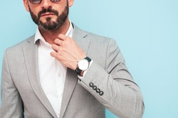 Closeup portrait of handsome confident stylish hipster lambersexual model.Sexy modern man dressed in elegant suit. Fashion male posing in studio near blue wall in sunglasses