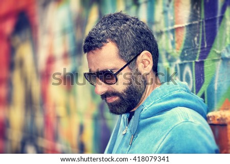 Closeup portrait of handsome man with stylish beard and sunglasses, standing over colorful city wall background, fashion street look, urban lifestyle #418079341