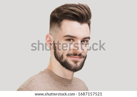 Closeup portrait of handsome smiling young man. Cheerful men isolated on gray background studio shot. Men model face with beard and modern haircut