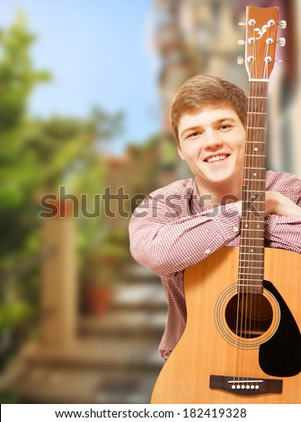 Closeup portrait of handsome young guitarist posing against summer street view