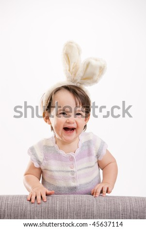 Closeup portrait of happy baby girl in easter bunny costume, laughing. Isolated on white background.