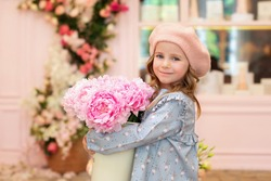 Closeup portrait of happy blonde little girl with long curly hair and in a beret with bouquet of pink peonies. Childhood concept. Celebration. cute child with flowers for mothers day. Celebration.