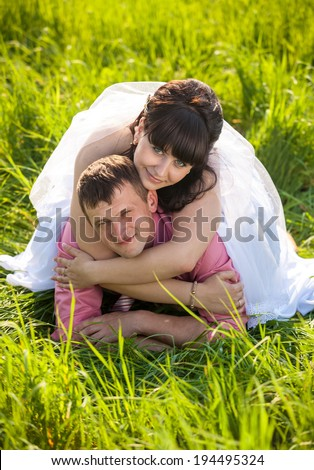 Closeup portrait of happy bride lying on grooms back at field