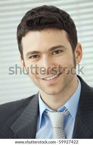 Closeup portrait of happy businessman wearing grey suit and blue shirt, looking at camera, smiling.