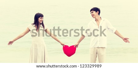 Closeup portrait of happy couple at the beach with heart. - stock photo