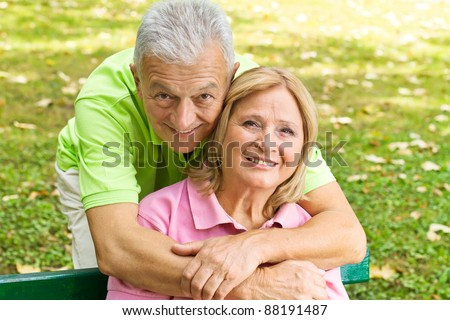 Closeup portrait of happy elderly man embracing mature woman. - stock photo