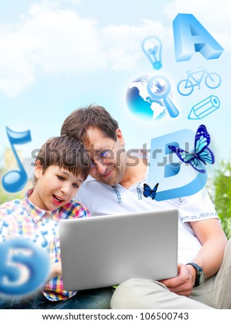 Closeup portrait of happy family: father and his son educating using laptop outdoor at their backyard sitting on the grass together