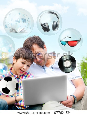 Closeup portrait of happy family: father and his son using laptop outdoor at their backyard sitting on the grass together. Different objects flying from the screen