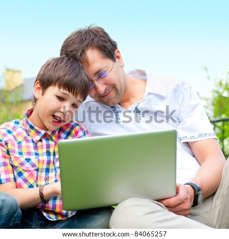 Closeup portrait of happy family: father and his son using laptop outdoor at their backyard sitting on the grass together