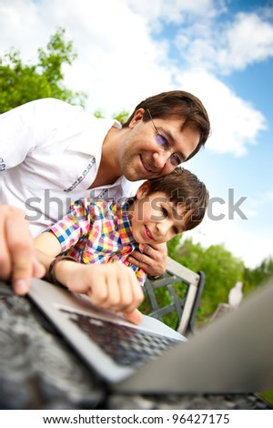 Closeup portrait of happy family: father and his son using laptop outdoor at their backyard sitting on the bench