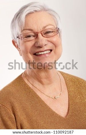 Closeup portrait of happy granny smiling in glasses and elegant sweater.