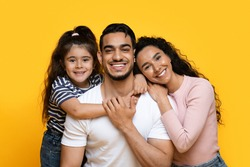 Closeup Portrait Of Happy Middle Eastern Family Of Three With Adorable Little Daughter, Joyful Middle Eastern Parents And Their Cute Female Child Embracing And Posing At Camera Over Yellow Background